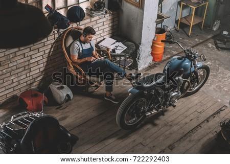 mechanic using digital tablet in repair shop with motorbike #722292403