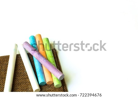 Education chalk put on brown fabric on white background #722394676