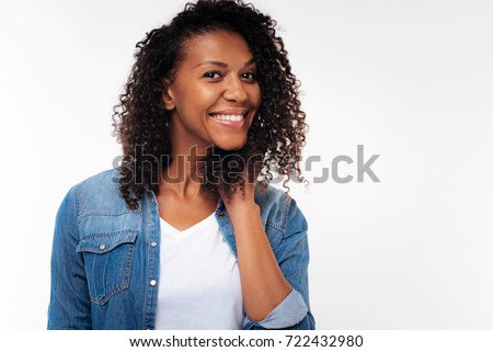 Cheerful curly woman holding hand in hair and smiling #722432980