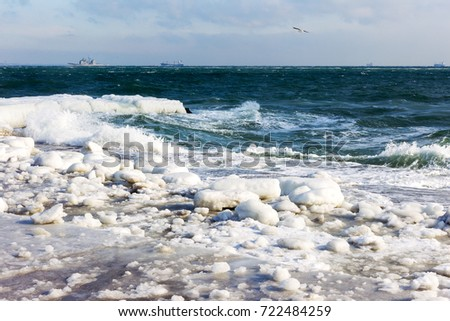 Winter seascape. Snow, ice huge waves beating against the shore and freezes. Natural disaster in form of storms and severe frosts led to icing of the black sea coast near Odessa.  #722484259