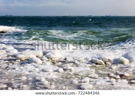 Winter seascape. Snow, ice huge waves beating against the shore and freezes. Natural disaster in form of storms and severe frosts led to icing of the black sea coast near Odessa.  #722484346
