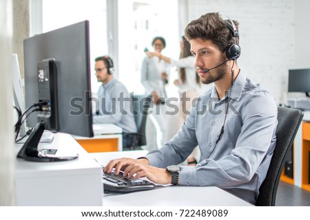 Young handsome male customer support phone operator with headset working in call center. Royalty-Free Stock Photo #722489089