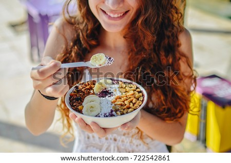 Acai bowl woman eating morning breakfast at cafe. Closeup of fruit smoothie healthy diet for weight loss with berries and oatmeal. Organic raw vegan healthy food. #722542861