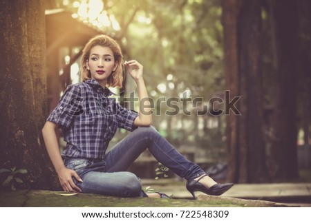 Beautiful girls in fashionable jeans and plaid shirts. She sat posing for a photo shoot at the camera. #722548309