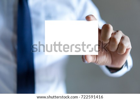 Man's hand showing business card - closeup shot on grey background #722591416