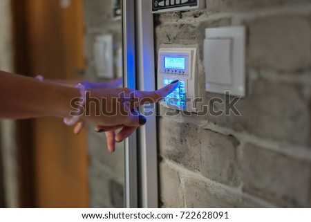 Home security system. Woman entering password on home alarm keypad #722628091