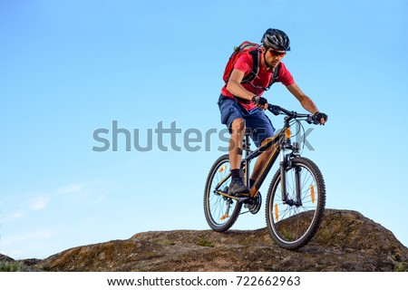 Cyclist in Red T-Shirt Riding the Bike Down the Rock on the Blue Sky Background.  #722662963