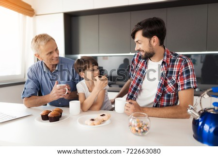 A man looks at the boy who sits in front of him and has a cookie. Behind the boy sits an old man with a mug of tea and look at them #722663080