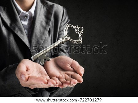 Cropped image of businessman in suit keeping big key in hands with dark wall on background. #722701279