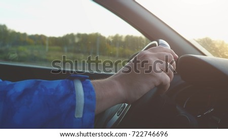 Male hand on steering wheel closeup. Man driving his car #722746696