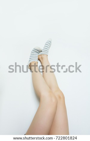 Striped Sock. Woman Slim Legs and Feet Wear Sock Striped on White Wall Background Great For Any Use. #722801824