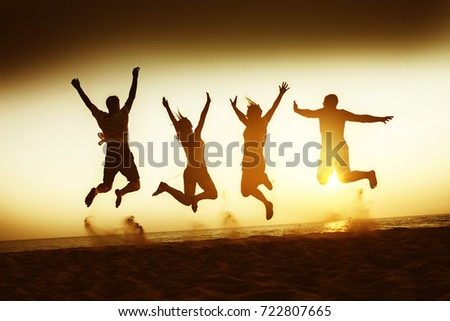 Four happy friends having fun and jumping at sunset beach #722807665
