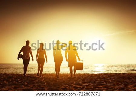 Friends travel concept. Four friends going to relax at sunset beach with stuff. Space for text #722807671