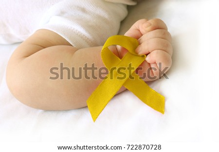 Childhood cancer awareness gold ribbon on human hand and baby background.Gold ribbon symbolic concept raising campaign support help childhood cancer awareness, Royalty-Free Stock Photo #722870728