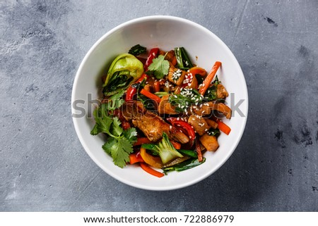 Chicken meat with vegetable in bowl stir fry on wok on concrete background #722886979