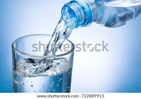 Pouring water from bottle into glass on blue background #722889913