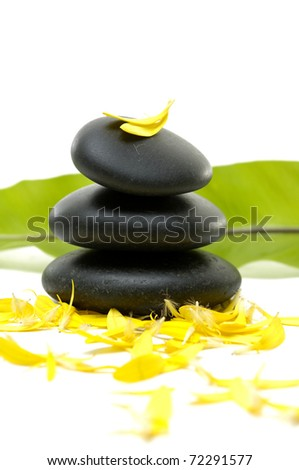 Stacked stones and green banana leaf with flower petals #72291577