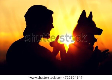 Young man and his dog friend having fun together, enjoying sunset time together. Travelling and vacation concept. #722924947
