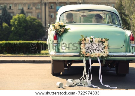 Wedding couple in car decorated with plate JUST MARRIED and cans outdoors #722974333