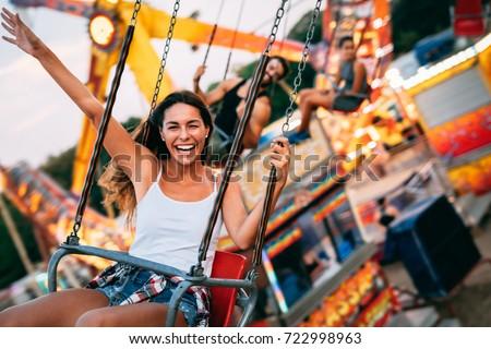 Beautiful couple having fun at amusement park. Soft focus, high ISO, grainy image.