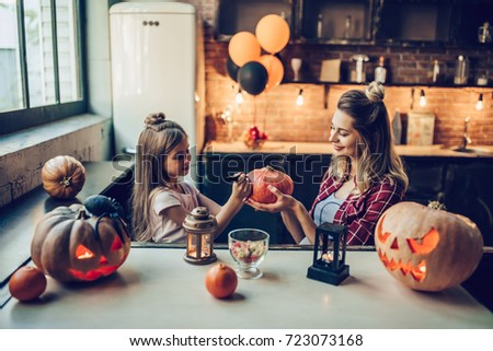 Happy Halloween! Attractive young pregnant woman with her little cute daughter are preparing to Halloween on kitchen. Mom with daughter are having fun with pumpkins while painting it. #723073168