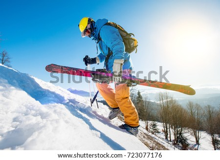 Male skier walking up the snowy hill in the Carpathians mountains carrying his skis copyspace seasonal activity sport sportsman hobby recreation travel concept #723077176