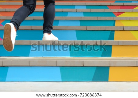 Lower part of teenage girl in casual shoe walking up outdoor colorful stair,teenage lifestyle successful concept Royalty-Free Stock Photo #723086374