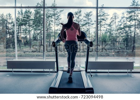 Attractive young sports woman is working out in gym. Doing cardio training on treadmill. Running on treadmill. #723094498