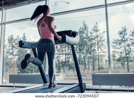 Attractive young sports woman is working out in gym. Doing cardio training on treadmill. Running on treadmill. #723094507