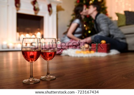 Two glasses of sparkling wine in front of warm fireplace. Cozy relaxed romantic atmosphere near fire of fireplace. A close picture of two wine glasses and a warm blurred kiss on the background.