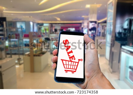 Hand holding smartphone with blur in shopping mall background. #723174358