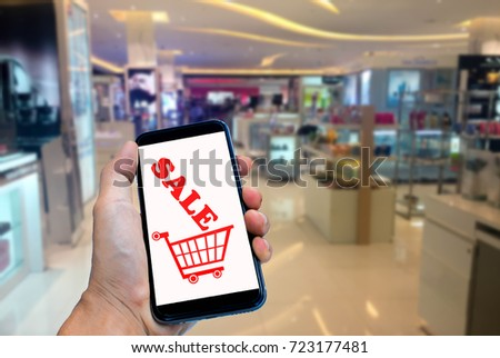 Hand holding smartphone with blur in shopping mall background. #723177481