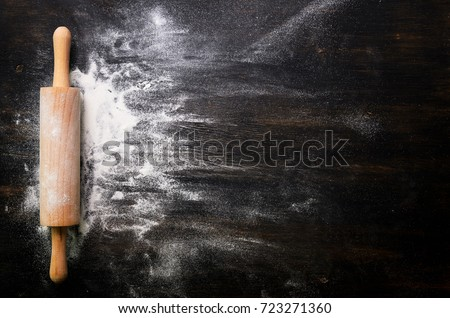 Baking background with free space for your text. Rolling pin and flour on black table. Copy space. Top view Royalty-Free Stock Photo #723271360