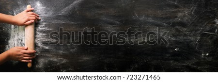 Girl hands keep rolling pin with flour on dark black table, baking background, top view, copy space for your text, meru, recipe. Banner #723271465