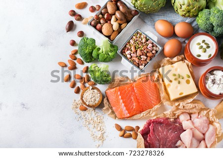 Assortment of healthy protein source and body building food. Meat beef salmon chicken breast eggs dairy products cheese yogurt beans artichokes broccoli nuts oat meal. Copy space background, top view