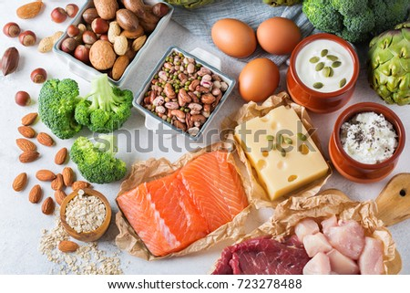Assortment of healthy protein source and body building food. Meat beef salmon chicken breast eggs dairy products cheese yogurt beans artichokes broccoli nuts oat meal. Top view