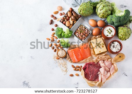 Assortment of healthy protein source and body building food. Meat beef salmon chicken breast eggs dairy products cheese yogurt beans artichokes broccoli nuts oat meal. Copy space background, top view #723278527