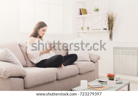 Young woman using smartphone at home on the couch. Dark-haired girl in casual texting online #723279397