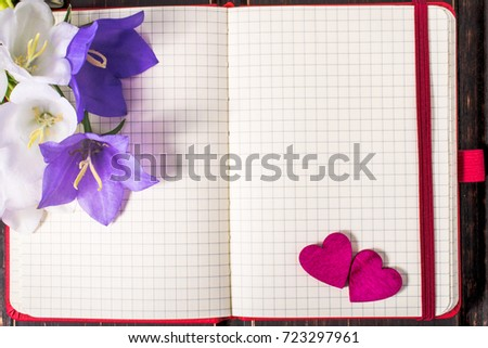 blank note book close-up with spring flowers, pink hearts and copy space on wooden background. summer border template. mock-up floral background. sale and greeting card concept. #723297961