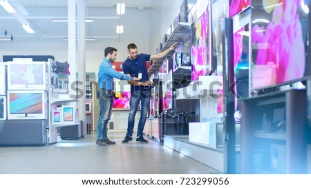 In the Electronics Store Professional Consultant Shows Latest TV's to a Young Man, They Talk about Specifications and What Model is Best for Young Man's Home. Store is Bright and Has Latest Models. Royalty-Free Stock Photo #723299056