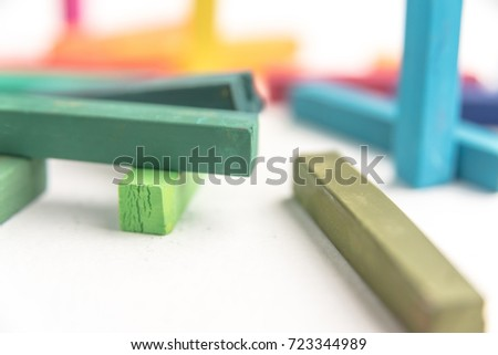 Macro of colored pastel chalks in a chaotic manner with selective focus, on white background #723344989