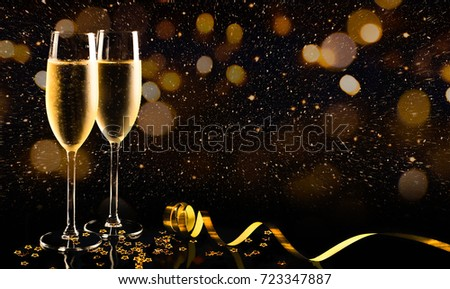 Two glasses of champagne with golden confetti, glitter, serpentine and lights. Night of celebration concept #723347887