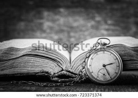 Decaying clock on the background of old shabby wise book. Black and white photography