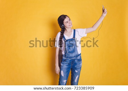 A teenage girl in headphones makes a selfie on a bright orange and yellow background. Place for your text. #723385909