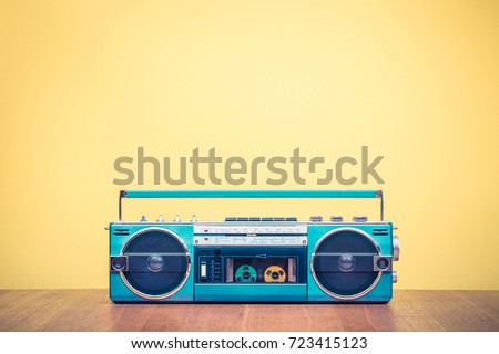 Retro outdated portable stereo mint green radio cassette recorder from 80s front yellow background. Vintage old style filtered photo #723415123