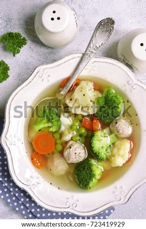 Soup with meatballs and vegetables in a vintage plate over light slate,stone or concrete background.Top view . #723419929