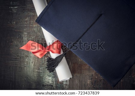 Graduation hat and diploma on table #723437839