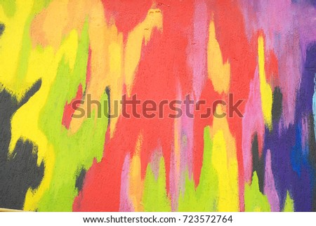 Wall apinted with multicolored Rainbow Paint. Yellow, Orange, Blue, Turquoise, Red, Sur, Black. Colored Paint that Flows. #723572764