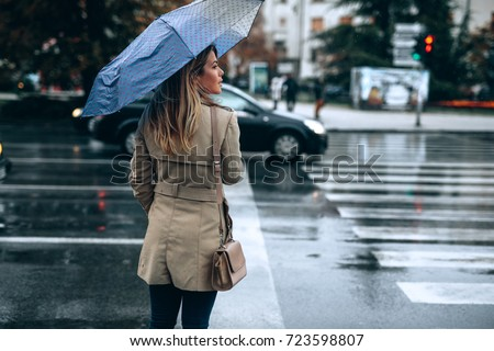 Beautiful woman with umbrella on a rainy day. #723598807