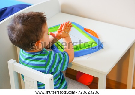 Two years old boy sitting by a table and using a sketcher on November 2015 in Poznan, Poland #723623236